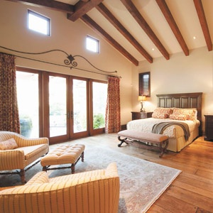 Master bedroom home improvement with wood beams in ceiling